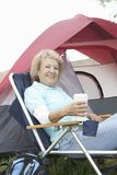 Senior Woman Having Coffee By Tent Stock Photography