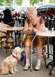 Senior woman having a cup of coffee. Senior woman sitting in cafe with a dog and having a cup of coffee stock photography