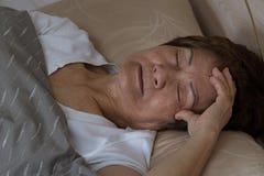 Senior woman having difficulty falling asleep at nighttime royalty free stock photo