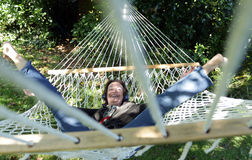Senior woman having fun in hammock. Senior woman having fun and listening to music in a hammock Royalty Free Stock Image