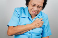 Senior woman having a heart attack. And grabbing her chest Stock Image