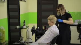 Senior woman having her hair dyed by beautician stock video