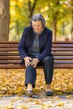 Senior woman having knee pain sitting on bench in park. Senior woman sitting on bench in autumn park and having knee pain. Arthritis pain concept. Focus on her royalty free stock photo