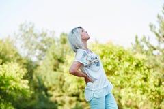 Senior woman having lumbago pain. In the nature in summer Royalty Free Stock Photos