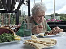 Senior woman having lunch in a cafe Stock Photos
