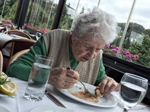 Senior woman having lunch in a restaurant Stock Images