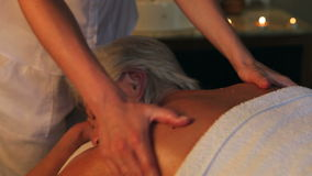 Senior Woman Having Massage In Spa. Camera tracks from senior woman relaxing with massage at beauty spa up to massage therapist.Shot on Canon 5d Mk2 with a frame stock video