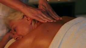 Senior Woman Having Massage In Spa. Camera tracks from senior woman relaxing with massage at beauty spa up to massage therapist.Shot on Canon 5d Mk2 with a frame stock video footage