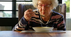Senior woman having soup on dining table at home 4k. Senior woman having soup on dining table at home. Woman blowing hot soup 4k stock video footage