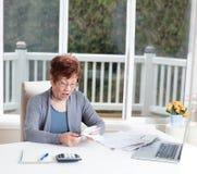 Senior woman having stress looking at her financial bills stock photography