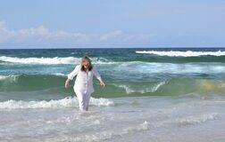 Senior woman playing sea gets surprised by cold surf wave
