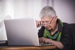 Senior woman, bad eyesight. Senior woman having troubles reading computer text, bad eyesight Royalty Free Stock Image