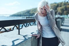 Senior woman having vertigo outdoors. Need to take my pills. Exhausted older lady leaning on a barrier and touching her forehead while suffering from a terrible Royalty Free Stock Photography