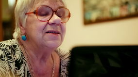 Senior woman having a video chat. Close-up shot of emotional senior woman in glasses having a video chat using laptop stock footage