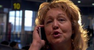 Senior woman having a vivid phone talk at airport stock video
