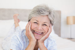 Senior woman with head in hands on bed Royalty Free Stock Image