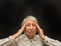 Senior Woman With Head In Hands Looking Weary. On black royalty free stock images
