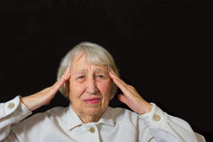 Senior Woman With Head In Hands Looking Weary. On black stock image