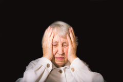 Senior Woman With Head In Hands Looking Weary. On black royalty free stock photography