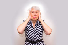Senior Woman With Head In Hands Looking Weary. At studio stock photo