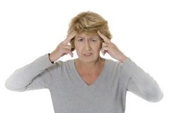 Senior woman with headache. Studio shot against a white background of a senior woman with bad headache or migraine Royalty Free Stock Photo