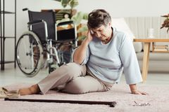 Senior woman with headache. Senior woman with a headache sitting on the floor and looking for her cane after falling down. Wheelchair in the background stock photo