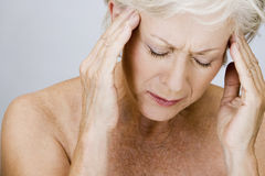 A senior woman with a headache, touching temples Royalty Free Stock Images