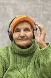 Senior woman with headphones listening to music. Stock Photo