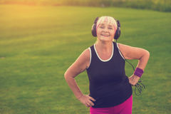 Senior woman in headphones. Smiling person outdoors. First album of favorite band. Songs that inspire royalty free stock photos