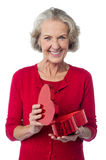 Senior woman with heart shaped gift box Royalty Free Stock Images