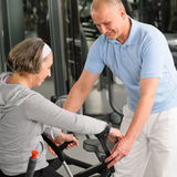 Senior woman with help of physiotherapist. Senior women with crutches getting help of physiotherapist at gym Stock Image