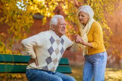 Senior woman helping senior man who has a back pain royalty free stock photos