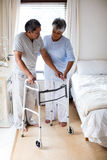 Senior woman helping senior man to walk with walker. At home Royalty Free Stock Image