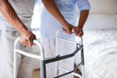Senior woman helping senior man to walk with walker at home Royalty Free Stock Images