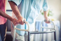 Senior woman helping senior man to walk with walker Royalty Free Stock Photos