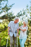 Senior woman helps man on crutches. Senior women helps an old men on crutches in the park Stock Photo