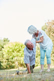 Senior woman helps a man having lumbago pain. Senior women helps men on his knees having a lumbago pain attack in the park in summer Royalty Free Stock Image
