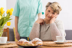 Senior woman in her apartment. Smiling senior women and her caregiver in an apartment royalty free stock image