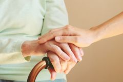 Senior woman with her caregiver at home. Old hands and young hands on cane close up. Concept senior people health care. Old woman hands and nurse hands. Elderly royalty free stock photo