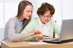 Senior woman with her daughter online purchasing. Together Royalty Free Stock Photos