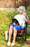 Senior woman with her dog ,drinking beer Stock Photos