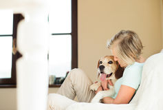 Senior woman with her dog at home relaxing Royalty Free Stock Photo