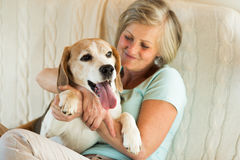 Senior woman with her dog at home relaxing Stock Photo