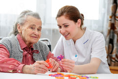 Senior woman with her elder care nurse. Elder care nurse playing jigsaw puzzle with senior women in nursing home Stock Photo