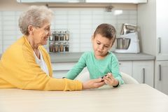 Senior woman with her grandson using digital glucometer. Diabetes control royalty free stock photos