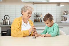 Senior woman with her grandson using lancet pen. Diabetes control. Senior woman with her grandson using lancet pen at home. Diabetes control royalty free stock photo