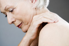 A senior woman with her hand on her shoulder Royalty Free Stock Photography