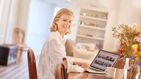 Senior woman in her office working on a laptop Stock Image