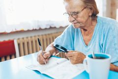 Senior woman enjoys solving a crossword puzzle Stock Photos