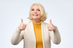 Senior woman in her 70s showing thumbs up gestures with both hands,. Looking at camera and smiling. Positive human emotion royalty free stock image